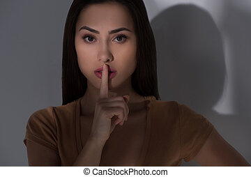 Keep silence. Beautiful young woman holding finger on mouth...