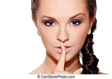"""Beauty headshot of a young woman showing gesture """"keep silence"""""""