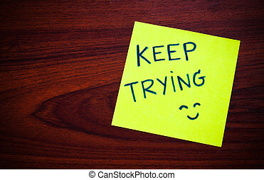 Keep trying on yellow sticky note against wood wall