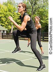 Keep ups - Young women exercising outdoors, doing keep ups