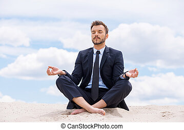 Keeping calm inside his soul. Handsome young businessman meditating while sitting in lotus position on sand and against blue sky