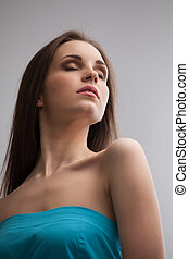 Keeping calm. Low angle view of beautiful young woman in blue dress keeping her eyes closed while standing isolated on grey background