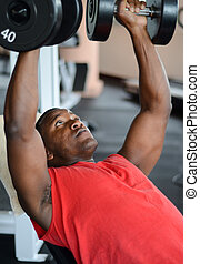 An African American man lifting dumbbells at the gym