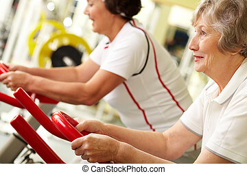 Tilt up of two active senior women doing fitness at gym