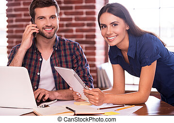Keeping friendly atmosphere at work. Cheerful young man and woman sitting at the working place and smiling while woman holding digital tablet and man talking on the mobile phone