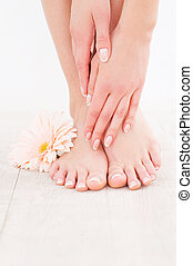 Keeping her feet clean and smooth. Close-up of woman touching her feet while standing on hardwood floor