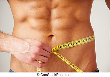 Keeping his body in fit. Close-up of muscular man measuring his waist with measuring tape while standing against grey background
