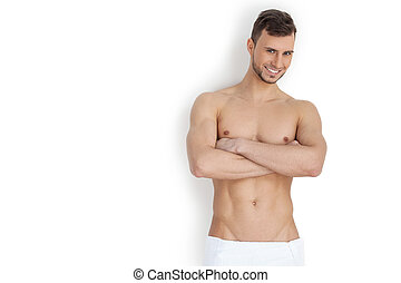 Keeping his body in good shape. Cheerful young muscular man looking at camera and keeping arms crossed while standing isolated on white background