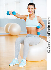 Keeping my body fit. Beautiful young woman in sports clothing exercising with dumbbells and smiling while sitting on fitness ball