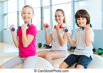 Keeping our bodies fit. Cheerful mother and two children exercising with dumbbells in health club while sitting on the fitness balls together