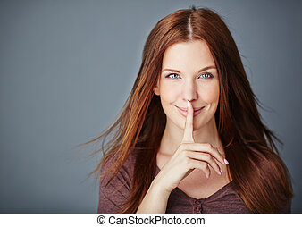 Young woman with dark long hair keeping her forefinger by lips