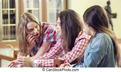 Keeping Secrets - Three girlfriends exchanging news at the...