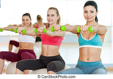 Keeping their bodies in shape. Three beautiful young women in sports clothing holding dumbbells and smiling at camera while sitting on the fitness ball