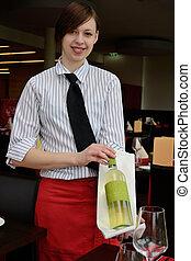 Kellnerin zeigt Weinflasche - Kellnerin praesentiert...