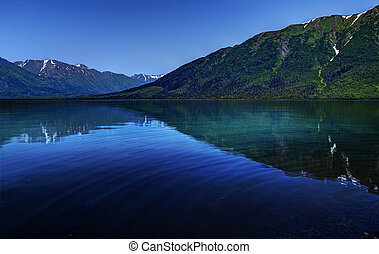 Kenai Lake in Alaska near Cooper Landing on a bright sunny day with mountain reflections in the water and a ripple with a bright blue sky.