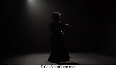 Kendo fighter performing martial art with Katana sword at...