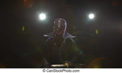 Kendo guru sitting on the floor in an traditional armor and...