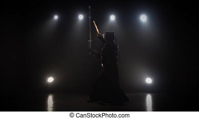 Kendo master wearing in an armor, black kimono and helmet is practicing martial art with bamboo Katana shinais at dark against spotlights with haze, slow motion.