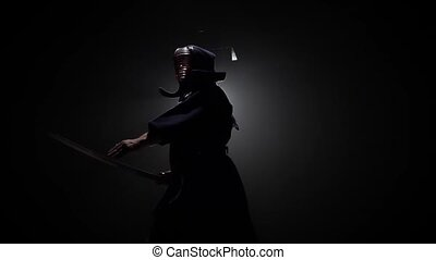 Kendo warrior is practicing martial art with the Katana...