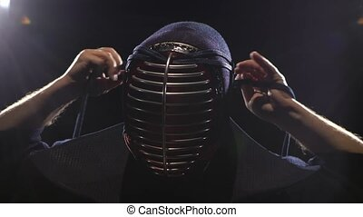 Kendo warrior is putting on helmet and lacing it. Close-up -...
