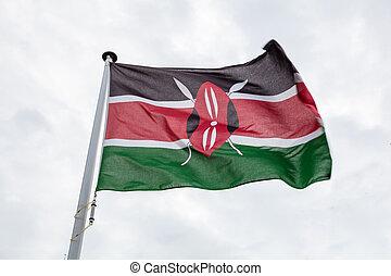Kenya flag on a pole waving, cloudy sky background