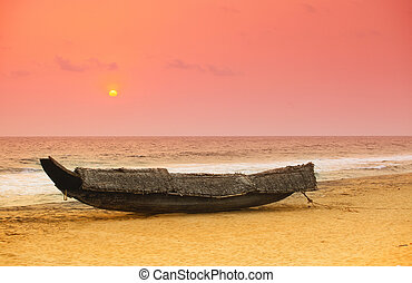 Kerala sunset - The sun sets behind a beached traditional ...