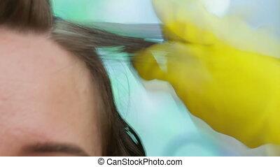 Two girls make keratin straightening hair at home.