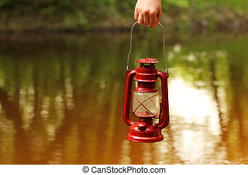 Kerosene lamp in hand against the background of the river