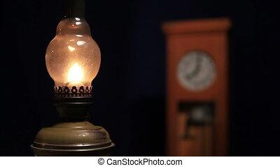 kerosene lamp on the background of the old clock