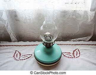 Kerosene lamp on the table near the window