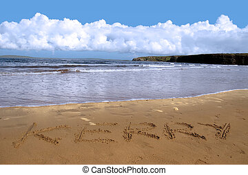 kerry inscribed on the beach with ocean waves and a cliffs in the background