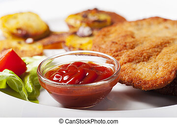 ketchup with a wiener schnitzel and roasted potatoes