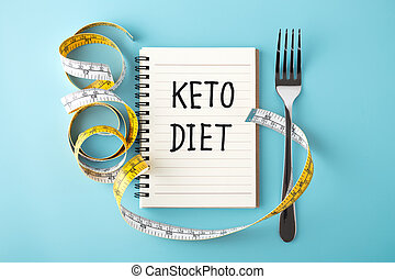 Keto diet word on notebook with measuring tape and fork on blue background