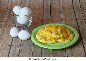 Keto Egg Bread on a wood plank board with a bowl of eggs -...