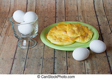 Keto Egg Bread, also called Oopsie Bread, on a plate with the main ingredient of eggs on the side