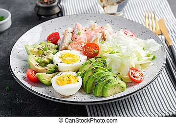 Ketogenic diet breakfast. Eggs, fish and avocado, lettuce ...