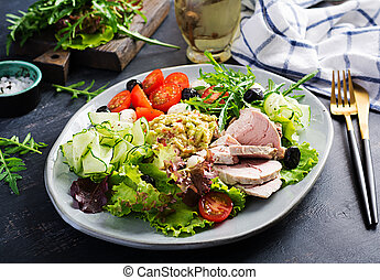 Ketogenic diet. Dinner dish with boiled pork meat, avocado guacamole, tomatoes, cucumbers, mozzarella cheese, black olives  and arugula. Detox and healthy concept. Keto food.