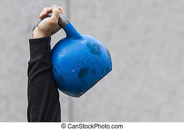 man holding a kettle bell used for crossfit