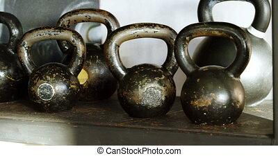 Kettle bells kept on the shelf in the fitness studio 4k -...