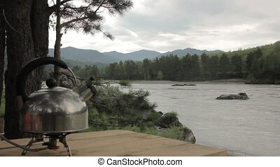 kettle boils on gas cooker on a river background.