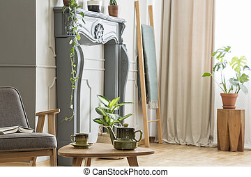 Kettle on wooden table next to grey armchair in retro living room interior with plants. Real photo