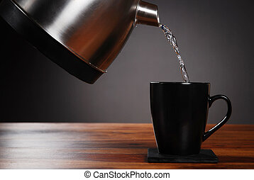 Kettle pouring water into mug on dark background