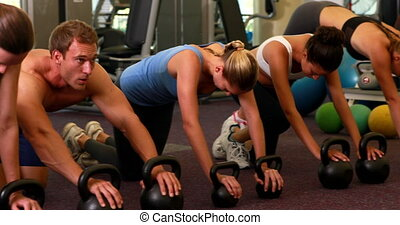 Kettlebell class getting into plank position at the gym