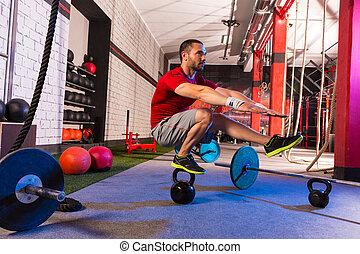 kettlebell man pistol squat balance at gym workout