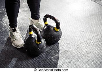 Kettlebell on floor. Girl training in gym