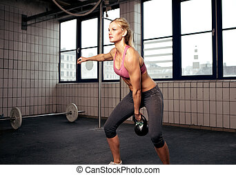 Kettlebell Workout - Young adult fitness woman doing swing...