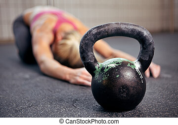 Kettlebell Workout - Young woman stretching her back after a...