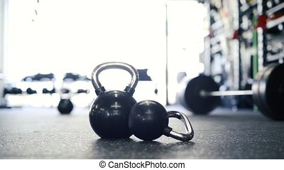 Kettlebells laid on the floor in modern gym. - Close up of...