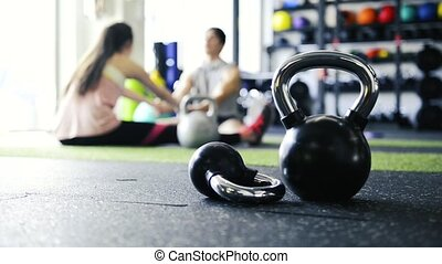 Kettlebells on the floor in gym. Couple stretching legs. -...