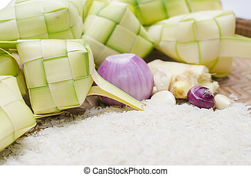 ketupat casing and rice in bamboo container. traditional...